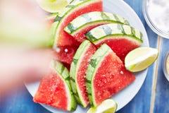 Zusammendrücken des Limettensaftes auf einem Stapel von Wassermelonenscheiben Lizenzfreies Stockfoto
