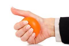 Zusammendrücken einer orange Druckkugel Lizenzfreies Stockfoto