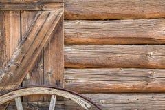 Zusammenfassung der Weinlese-Antiken-Blockhaus-Wand und des Lastwagen-Rades Lizenzfreie Stockfotografie