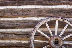 Zusammenfassung der Weinlese-Antiken-Blockhaus-Wand und des Lastwagen-Rades Stockfotografie