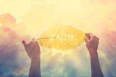 Zusammenfassung, ein gelbes Blatt im bunten Himmel des Glaubens halten, Weinlesefarbton Stockbilder