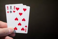 Zusammenfassung: Mann, den die Hand, die Spielkarte drei acht hält, auf schwarzem Hintergrund mit copyspace Poker lokalisierte, s Lizenzfreie Stockbilder