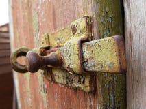 Zusammenfassung mit dem Bolzen und rustes auf ihm auf der Holztür Lizenzfreie Stockbilder