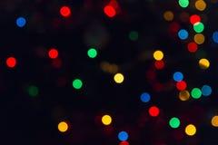 Zusammenfassungs-festliches neues Jahr-Weihnachtsdefocused Hintergrund mit bokeh mehrfarbigem Effekt auf schwarzen Hintergrund mi stockfotos
