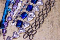 Zusammengebaute Perlen und Ketten in der kurzen Armbandlänge auf goldenem Hintergrund Lizenzfreie Stockfotografie