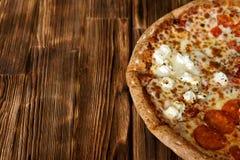Zusammengesetzt-sortierte Pizza auf einer nat?rlichen Holzoberfl?che von Kiefernbrettern Tageslicht Nahaufnahme Freier Raum zu un lizenzfreies stockbild