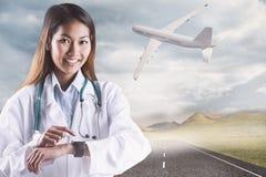 Zusammengesetztes Bild asiatischen Doktors, der ihre intelligente Uhr verwendet Stockbild