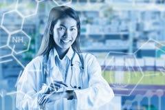 Zusammengesetztes Bild asiatischen Doktors, der ihre intelligente Uhr verwendet Stockfotografie
