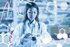 Zusammengesetztes Bild asiatischen Doktors, der ihre intelligente Uhr verwendet Lizenzfreie Stockfotos