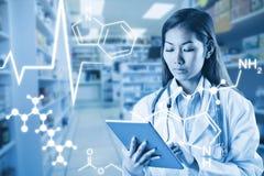 Zusammengesetztes Bild asiatischen Doktors, der Tablette verwendet Lizenzfreie Stockbilder