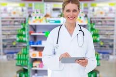Zusammengesetztes Bild blonden Doktors, der Tabletten-PC verwendet Stockfotos