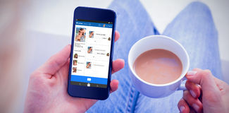 Zusammengesetztes Bild 3d der Frau, die ihren Handy verwendet und Tasse Kaffee hält Stockbilder