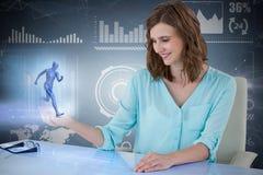 Zusammengesetztes Bild 3d der lächelnden Geschäftsfrau sitzend am Schreibtisch und digitalen Schirm verwendend stockfotografie