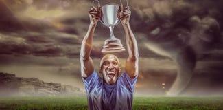 Zusammengesetztes Bild 3D des glücklichen Athleten zujubelnd beim Halten der Trophäe Stockbild