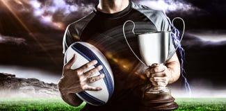 Zusammengesetztes Bild 3D des Mittelteils des erfolgreichen Rugbyspielers, der Trophäe und Ball hält Stockbilder
