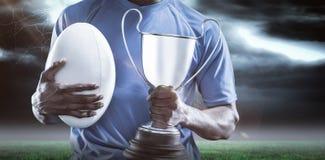 Zusammengesetztes Bild 3D des mittleren Abschnitts des Sportlers Trophäe und Rugbyball halten Lizenzfreies Stockfoto