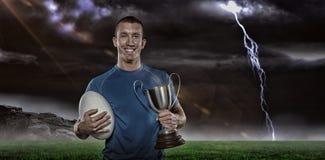 Zusammengesetztes Bild 3D des Porträts des lächelnden Rugbyspielers, der Trophäe und Ball hält Stockbild