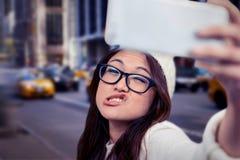 Zusammengesetztes Bild der asiatischen Frau Gesichter machend und selfie nehmend Lizenzfreie Stockbilder
