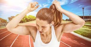Zusammengesetztes Bild der Athletenfrau ihr Haar binden und Musik hörend lizenzfreies stockfoto