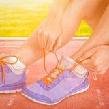 Zusammengesetztes Bild der Athletenfrau ihre Laufschuhe binden stockbilder