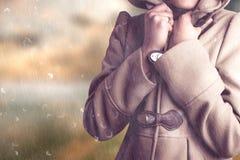 Zusammengesetztes Bild der attraktiven Frau einen warmen Mantel mit der Haube tragend angehoben lizenzfreie stockfotos
