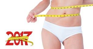 Zusammengesetztes Bild der attraktiven Frau ihren Bauch messend Lizenzfreie Stockfotografie