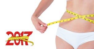 Zusammengesetztes Bild der attraktiven Frau ihren Bauch messend Stockfotografie