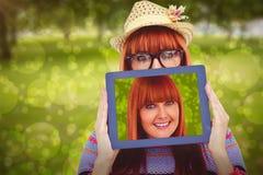 Zusammengesetztes Bild der attraktiven Hippie-Frau hinter einer Tablette stockfotos