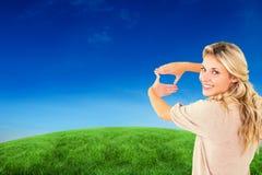 Zusammengesetztes Bild der attraktiven jungen blonden Gestaltung mit ihren Händen Lizenzfreies Stockbild