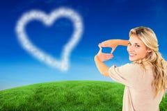 Zusammengesetztes Bild der attraktiven jungen blonden Gestaltung mit ihren Händen Lizenzfreies Stockfoto
