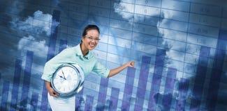 Zusammengesetztes Bild der begeisterten Geschäftsfrau eine Uhr halten Lizenzfreie Stockfotos
