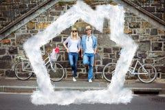 Zusammengesetztes Bild der bereitstehenden Backsteinmauer der jungen Paare der Hüfte mit ihren Fahrrädern Stockfoto