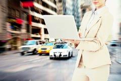Zusammengesetztes Bild der überzeugten Geschäftsfrau Laptop halten Lizenzfreies Stockfoto
