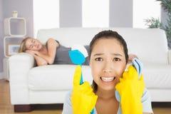 Zusammengesetztes Bild der beunruhigten Frau, die Stoff und Schrubber hält Stockfotos