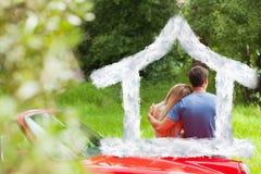 Zusammengesetztes Bild der bewundern Natur der liebevollen Paare beim Lehnen auf ihrem Cabriolet Stockfotografie