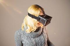 Zusammengesetztes Bild der blonden Frau, die Kopfhörer der virtuellen Realität verwendet Lizenzfreie Stockfotografie