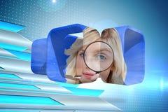 Zusammengesetztes Bild der blonden haltenen Lupe auf abstraktem Schirm Stockfotografie