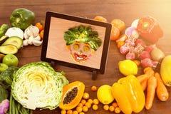 Zusammengesetztes Bild der digitalen Tablette umgeben mit frischen Obst und Gemüse stock abbildung