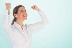 Zusammengesetztes Bild der erfolgreichen Geschäftsfrau mit den geballten Fäusten, die oben schauen Stockfotografie