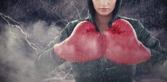 Zusammengesetztes Bild der ernsten jungen Frau in den roten Boxhandschuhen und in der schwarzen Haube Stockbilder