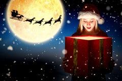 Zusammengesetztes Bild der festlichen Blondine ein Geschenk halten lizenzfreie stockbilder