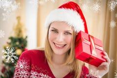 Zusammengesetztes Bild der festlichen Blondine ein Geschenk halten Stockfoto