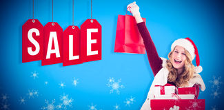 Zusammengesetztes Bild der festlichen Blondine mit Einkaufstasche und Geschenken Lizenzfreies Stockbild