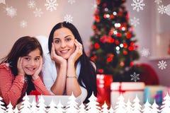 Zusammengesetztes Bild der festlichen Mutter und der Tochter, die an der Kamera lächelt Stockfoto