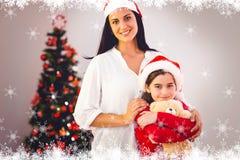 Zusammengesetztes Bild der festlichen Mutter und der Tochter, die an der Kamera lächelt Stockfotografie