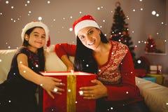 Zusammengesetztes Bild der festlichen Mutter und der Tochter, die ein glühendes Weihnachtsgeschenk öffnet Lizenzfreie Stockfotos