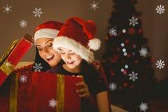 Zusammengesetztes Bild der festlichen Mutter und der Tochter, die ein Weihnachtsgeschenk öffnet Stockfotos