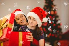 Zusammengesetztes Bild der festlichen Mutter und der Tochter, die ein Weihnachtsgeschenk öffnet Lizenzfreies Stockfoto