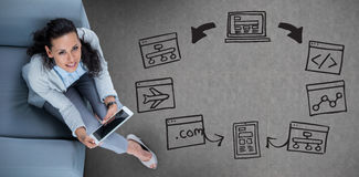Zusammengesetztes Bild der Frau auf ihrer Tablette, die oben schaut lizenzfreie stockfotografie
