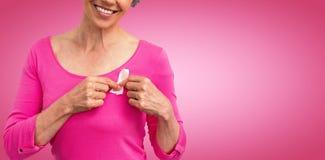 Zusammengesetztes Bild der Frau in den rosa Ausstattungen, die Band für Brustkrebsbewusstsein zeigen lizenzfreie stockfotografie